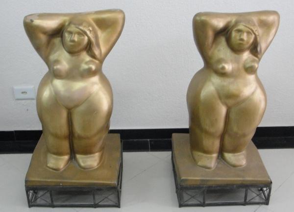 FC000, Par de esculturas antigas em metal com patina de bronze, representando figuras, medindo 85 cm de altura x 43 cm de largura cada, pesando aproximadamente 50 kg cada.