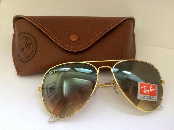 abda7fdba Belíssimo óculos modelo aviador, estilo Ray-Ban. Armação dourada, lentes na  cor marrom, hastes transparentes.