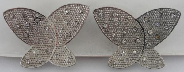 AM000, Par de broches, em metal prateado com pedrarias, medindo 4 x 3 cm cada.