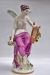 """MEISSEN SÉCULO XX - """"Cibele"""". Escultura de porcelana policromada representando figura feminina com asas e  lira nas mãos. Altura 46 cm. Com restauro."""