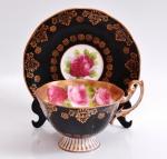 ROYAL ALBERT - Xícara com pires para chá, porcelana inglesa, fundo preto, no centro uma rosa e bordas douradas. Marcado no fundo.