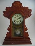 Relógio de mesa de madeira da marca Ansonia. Altura 56 cm comprimento 37 cm. Pequenos faltantes na parte superior da caixa.