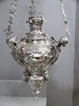 Magnífico lampadário de prata portuguesa lavrada, cinzelada e repuxada, P.Coroa, D.João, decorado com querubins alados, volutas, plumagens, conchoides e estilizações fitoformes em alto e baixo relevo. Mede 48 x 48 x 132 cm altura. Pesando 9.960 kg.