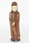 """Figura entalhada em madeira representando """"Gueixa"""", com rosto, mãos e pés em marfim, século XIX.  Manto com delicado entalhe. Apresenta fissuras na madeira e no rosto feitas pelo tempo. Alt.: 27 cm."""