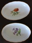 Duas travessas fundas em porcelana alemã manufatura de Maissen. Borda recortada com friso dourado, centro esmaldado com flores em policromia. Medidas: 23 X 15 cm.