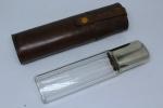 Cantil em fino vidro facetado, tampa espessurada a prata. Peça acondicionada em estojo de couro. Alt.: 19,5 cm.