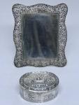 Duas peças sendo Porta retrato em prata filigranada, possivelmente francesa e linda caixa em prata alemã contrastada, cinzelada com instrumentos musicais e cesta de flores. Peso: 123 g. Medidas: 13 X 11 cm.