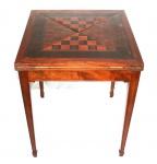 Mesa de jogo no estilo inglês, em madeira nobre marchetada para dama e xadrez. Tampo envelope. Medidas: 74 X 60 X 60 cm.