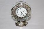 OCTO WATCH Cº. Relógio suíço de mesa com despertador em prata alemã. Mostrador em porcelana. (Mecanismo necessitando de revisão e corpo com mossa). Alt.: 9,5cm.