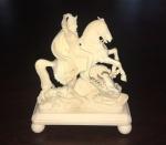 """Figura esculpida em marfim europeu representando """"São Jorge vencendo o Dragão"""". Medidas: 10 x 8 cm."""
