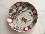 Prato de sobremesa em porcelana Japonesa, Imari - cerca de 1900. Borda recortada predominando a tonalidade rouge de fer, centro decorado com figura de animal e bambus.