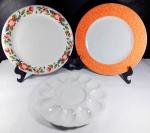 Lote contendo 1 prato porta ovos e 2 pratos rasos de manufaturas diferentes, todos em porcelana. Maior tamanho 26 cm de diâmetro.