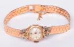 EMBE - 18 Quilates -Lindo e antigo relógio de pulso feminino, pulseira em ouro, caixa com incrustações de brilhantes., mostrador branco com ponteiros e números em ouro, acondicionado em caixa original. Med.: 16 cm.