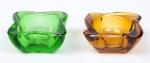 Lote constando dois delicados cinzeiros em vidro sendo um na cor verde com lapidação no fundo no padrão estrela e borda ondulada e um na cor âmbar com borda ondulada. Med:  0,05 x 0,08 cm. ( cada )