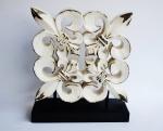 Escultura de madeira entalhada representando flor de liz. Medida; 24x27cm