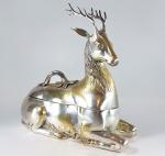 MOTTAHEDED & COMPANY ( NY - USA)  - Grande e muito pesada caixa em bronze no formato de Cervo descansando, ao gosto oriental. Alça nas costas. Originalmente dourada. A marca da grife se perdeu após o banho de prata dado pelo proprietário anterior. Peso 6 quilos. Med. 36 x 35 x 16 cm.  Preço usado em média de 450 dólares a 750 dólares. Ver ---------->     https://www.ebay.com/itm/Signed-Mottahedeh-Massive-Brass-Resting-Reindeer-Stag-Deer-Tureen-Covered-Box-/401367585215?_ul=BR   ....................................... A Mottahedeh & Company é uma empresa de Nova York que fabrica louças e acessórios decorativos. A empresa fez porcelana para o Presidente dos Estados Unidos, o Departamento de Estado dos EUA e o Corpo Diplomático. A empresa, com mais de 85 anos de idade, foi comprada da propriedade Mottahedeh em 1992. Hoje, é o líder reconhecido em reproduções antigas e adaptações em cerâmicas de luxo, principalmente porcelana dura e metais. É especializada em porcelana chinesa de exportação e porcelana europeia. Possui licenças com o Metropolitan Museum of Art, a Colonial Williamsburg Foundation, a Historic Charleston Foundation, a Mount Vernon Ladies Association, o Winterthur Museum and Gardens e o Tony Duquette, e tem um histórico de trabalhar com muitos mais. A licença mais recente é com a National Geographic Society .  VER MAIS DESTA PEÇA: https://www.worthpoint.com/worthopedia/signed-mottahedeh-massive-brass-1933745869