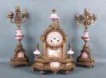 Linda garniture composta de um relógio e par de castiçais. Em bronze artisticamente trabalhado e complementos de porcelanas delicadamente pintadas a à mão. Mede o relógio 41cm de altura, castiçais 43cm de altura. Relógio não testado.