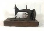 máquina de costura antiga em ferro e metal sobre base fixa de madeira década de 20-30 medindo 25 cm de altura por 40 de comprimento e 20 de largura.