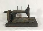 máquina de costura antiga em ferro e metal sobre base fixa de madeira década de 20-30 medindo 22 cm de altura por 36 de comprimento e 20 de largura.
