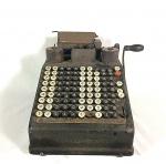 máquina de calcular antiga em ferro e metal Burroughs Portable década de 50 medindo 21 cm de altura por 33 de comprimento e 26 de largura.
