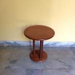 mesa redonda de apoio em madeira sobre tres pés roliços medindo 45 cm de altura por 41 de diâmetro.