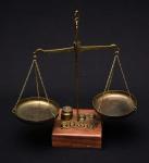 Balança, dita de ourives, com corpo em bronze, base de madeira e contrapesos em bronze.Medida 23x22cm. Peça completa e em excelente estado.