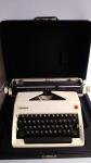 Máquina de escrever marca OLYMPIA em estojo original. Apresenta rolo do carrinho sem girar, lote vendido no estado.