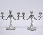 Par de candelabros de três lumes em prata portuguesa, contraste Águia 1º título. Corpo liso com detalhes em volutas. Med. 23 cm de altura. Peso 1.385 gr.