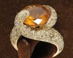 Anel em ouro amarelo 18 k. Diferente design de serpentes estilizadas cravejadas de safiras amarelas, entrelaçando um topázio de 5 kt  aproximadamente. Aro 12. Peso 11,9 gr. ( Por questão de segurança esse item não se encontra em nossa loja ).
