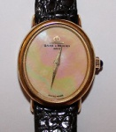 BAUME & MERCIER GENÉVE.  Relogio feminino em Ouro 18 K , contrastado, mostrador em nacre, com pulseira em couro com fivela original, caixa mede  2,5 x 2 cm.Numero de série 82424138232.