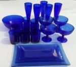 Vinte peças antigas em vidro azul, com três travessas, um bowl,cinco taças altas, sete copos e quatro taças de sobremesas.