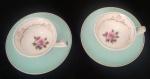 Par de delicadas xícaras em porcelana na cor azul clarinho ao fundo da xícara com flores