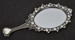 Espelho para toucador, de mão, confeccionado em metal com esmaltagem perolada e aplicações em estrasse. Med.: 21x10,5 cm.