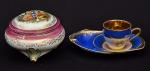 """Lote constando duas peças em porcelana policromada, sendo um púcaro e uma chávenacom cinzeiro em porcelana """"Luiz XV"""". Med.: 10x13 cm e 7x17 cm."""