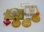 Quatro vidros perfumeiros, uma bandeija de metal , uma bandeja decorada um porta vela em vidro.