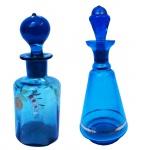 Lote com duas garrafas em vidro na cor azul com decorações. Maior 18 cm e menor 13 cm de altura.