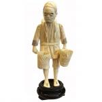 Escultura executada em marfim sobre base de madeira representando homem com cestos. Assinada. Japão, cerca de 1900. 17,5 com base e 15,5 sem base. Apresenta certificado.