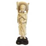 Escultura executada em marfim sobre base de madeira representando guerreiro. China, princípio do Séc. XX. 23 cm sem base e 26 cm com base. Apresenta certificado.