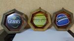 Trio de Quadros temáticos de Bebidas importadas, formato irregular na moldura em madeira, fixação para pendurar, com diâmetro de 29 centímetros, sem uso.