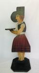 Simpática e decorativa peça em madeira com graciosa pintura para uso como mesa auxiliar. Figura feminina. Aprox.86 cm de altura.