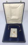 Livro de oração com capa em madrepérola, refilo em ouro e acompanha terço folheado a ouro, caixa original.