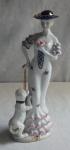 PORCELANA  Escultura Importada de dama com vestido branco, decorado com florais, manga e extremidade do vestido em babados com as bordas rosa, jovem segurando uma flor, sobre a cabeça um chapéu azul cobalto com filete dourado e uma flor, acompanha a jovem seu cachorro conduzido pela coleira e corrente. Alt. 32cm