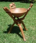"""ART AFRICANA - Escultura em madeira na forma de suporte para bowl, com base tríptica retorcida e entrelaçada, com acabamento superior representando """"elefantes"""". Med. total: 31 X 26 cm; e Med. bowl: 19 cm de diâmetro."""