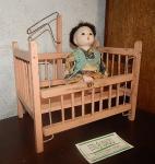 Berço de brinquedo  em madeira (Moreno Ind de Brinquedos SP / med al24 x 23 x15 cm ) e   boneco oriental (de massa med 20x13 cm )  com pés e braços articuláveis. (desgastes)