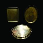Conjunto com 3 bandejas em metal  cinzelado e dourado. Exemplares com algumas marcas e manchas do tempo. Dimensões: Bandeja retangular 36 cm x 29 cm / Bandeja circular 44 cm diâmetro / Bandeja oval 45 cm x 32 cm.