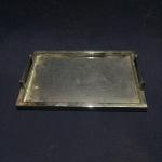 Bandeja retangular em metal prateado e vidro com alças. Apresenta pequenos arranhões. Dimensões: 36 cm x 25 cm.