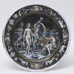 França SÉC XVIII / XIX, Prato esmaltado representando Julgamento de Páris, inteiramente pintado à mão, verso apresenta cavalheiro com elmo, pequena falta no esmalte. Medindo 21 cm de diâmetro.