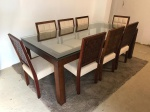 Mesa de jantar com tampo de vidro e conjunto de 8 cadeiras em madeiras com estofados em tom claro. Med. mesa 77,5x200x110 cm.