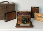 Câmera fotográfica francesa de viagem, toda em mogno envernizado com metais dourados, fole couro vermelho perfeito, lente perfeita. 2 magazines e negativo, mala original de couro e metais dourados.