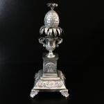 Belíssimo paliteiro em prata fundida, ricamente cinzelada e contrastada representando ânfora com folhas e abacaxi. Portugal, meados do Séc. XIX. 21 cm de altura.